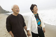 Senior couple on beach holding hands Stock Photos