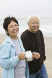 Senior couple on beach holding hands and looking at camera Royalty Free Stock Images
