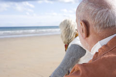 Senior couple on beach, looking out to sea, close-up, rear view Stock Photos
