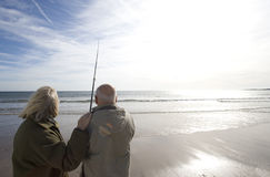 Senior couple on beach looking out to sea, man with fishing rod, rear view (lens flare) Stock Image