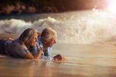 Senior couple on beach. Portrait of a senior couple lying on sandy beach Royalty Free Stock Photo
