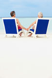 Senior Couple On Beach Relaxing In Chairs Royalty Free Stock Images
