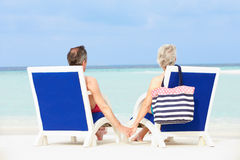 Senior Couple On Beach Relaxing In Chairs Stock Photo