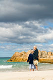 Senior Couple at Beach with Storm-clouds Gathering Royalty Free Stock Photos