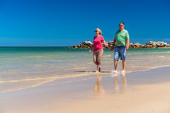 Senior couple at the beach. Senior couple walking at the beach holding hands of each other Royalty Free Stock Photo