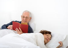 Senior couple in bed. Man reading and woman is asleep Royalty Free Stock Photo