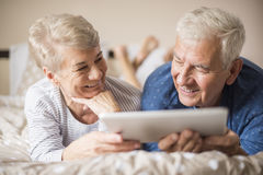 Senior couple in the bed. Senior adults browsing the Internet together Stock Photography