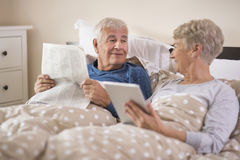 Senior couple in the bed. Both looking for some news on the Internet Royalty Free Stock Image