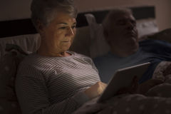 Senior couple in the bed. Grandmother browsing the Internet late at the night Stock Images