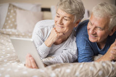 Senior couple in the bed. Senior couple looking for something in the Internet Stock Images