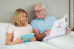 Senior couple on bed reading newspaper and book Stock Image