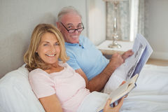 Senior couple on bed reading newspaper and book Royalty Free Stock Photography
