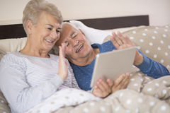 Senior couple in the bed. Seniors having a joyful video conference Stock Photography