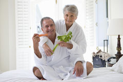 Senior couple in bedroom holding celery and carrot sticks, smiling, portrait Royalty Free Stock Photography