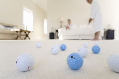 Senior couple in bedroom, man practising golf putt, focus on golf balls in foreground Stock Photography