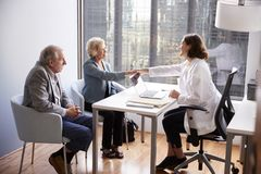 Free Senior Couple Being Greeted By Female Doctor With Handshake On Visit To Hospital For Consultation Stock Photos - 144590193