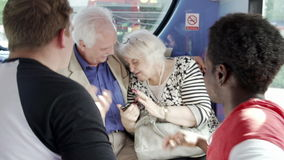 Senior Couple Being Harassed On Bus Journey. Two young men bullying senior couple on bus and trying to steal mobile phone in slow motion.Shot on Sony FS700 in stock video footage