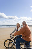 Senior couple with bicycles on beach, smiling at each other Royalty Free Stock Image
