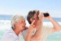 Senior couple bird watching. At the beach Royalty Free Stock Photos