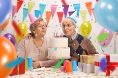 Senior couple with a birthday cake. Senior couple blowing candles on a birthday cake Stock Images