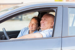 Senior couple in  black car. Stock Photos