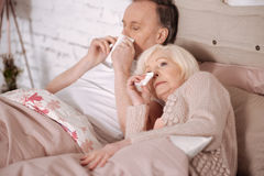 Senior couple blowing noses on bed Royalty Free Stock Photos