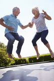 Senior Couple Bouncing On Trampoline In Garden Stock Images