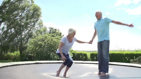 Senior Couple Bouncing On Trampoline In Slow Motion