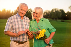 Senior couple with bouquet smiling. Stock Photography