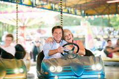 Senior couple in the bumper car at the fun fair Royalty Free Stock Photography
