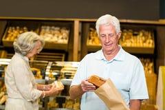 Senior couple buying bread Stock Images