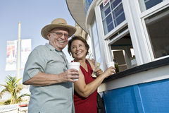 Senior Couple Buying Drinks At Food Stand Royalty Free Stock Photo