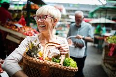 Senior couple buying fresh vegetables and fruits at the local market. Senior couple buying fresh vegetables at the local market stock image