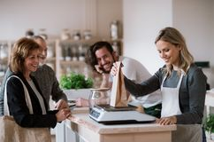 Senior couple buying groceries in zero waste shop, sales assistants serving them. Senior couple customers buying groceries in zero waste shop, sales assistants royalty free stock image
