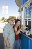 Senior Couple Buying Hot Dog At Food Stand Royalty Free Stock Photography