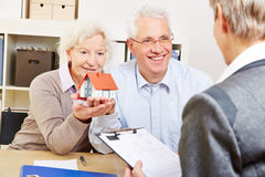 Senior couple buying real eastate. Happy senior couple with little house buying real eastate in office Stock Images