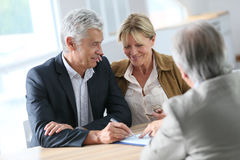 Senior couple buying a real-estate property. Senior couple meeting real-estate agent for investment Stock Images
