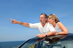 Senior couple in cabriolet admiring sea view Royalty Free Stock Photos