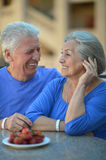 Senior couple in cafe with strawberries Stock Photos