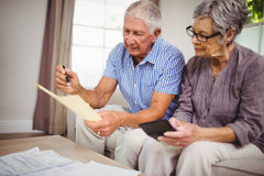 Senior couple calculating bills in living room Stock Images