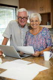 Senior couple calculating their invoices with laptop in the kitchen. At home Royalty Free Stock Photography