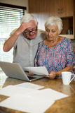 Senior couple calculating their invoices with laptop in the kitchen. At home Stock Photos