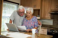 Senior couple calculating their invoices with laptop in the kitchen. At home Stock Photography