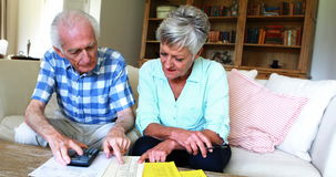 Senior couple calculating their invoices in the living room. At home