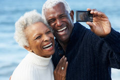 Senior Couple With Camera On Beach Royalty Free Stock Photo