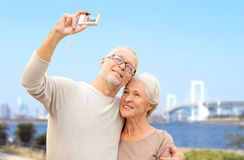 Senior couple with camera over rainbow bridge Royalty Free Stock Image