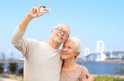 Senior couple with camera over rainbow bridge Royalty Free Stock Image