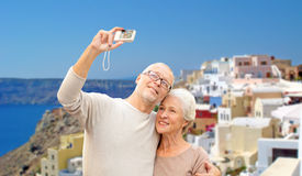 Senior couple with camera travelling in santorini. Tourism, travel and people concept - happy senior couple with camera taking selfie over santorini island Royalty Free Stock Images