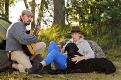 Senior couple camping and enjoying music Royalty Free Stock Photo