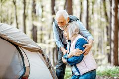 Senior couple camping in the forest. Senior couple hugging during the picnic at the campsite in the forest royalty free stock image